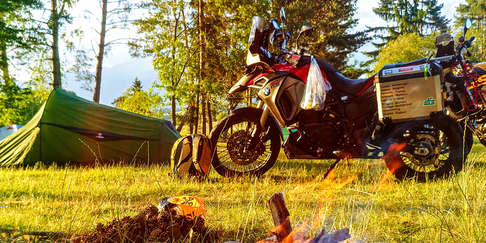 Motorrad und Zelt am Lagerfeuer
